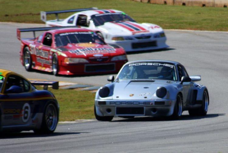Aaron Hudson, 74 Porsche 911 RSR in a crowd.