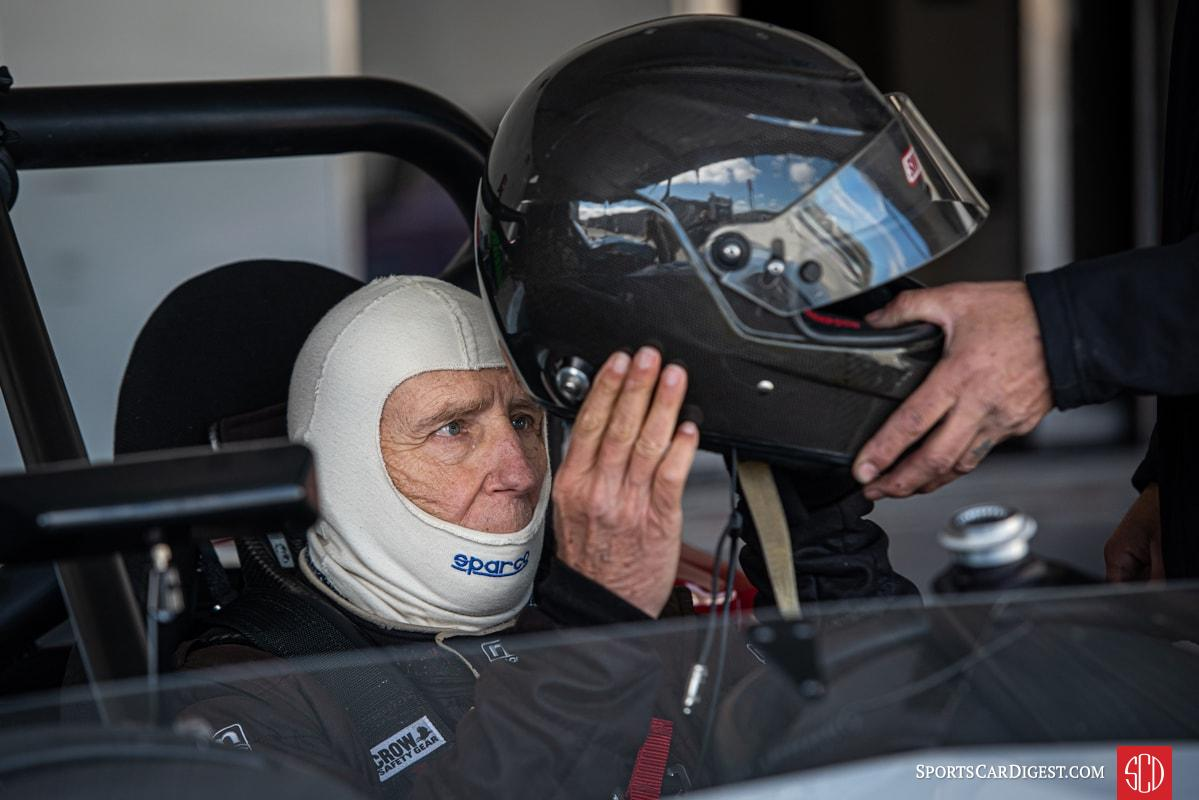 A driver prepares to don his full face helmet before hitting the track